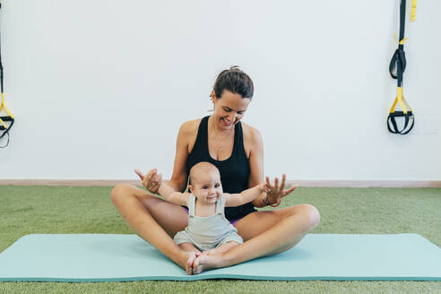 Young mother and baby exercising on yoga mat - MPPF00277