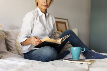 Mature woman with book and coffee cup sitting on bed at home - VABF02332