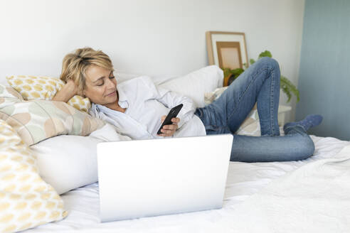 Mature woman lying on bed at home using smartphone and laptop - VABF02353