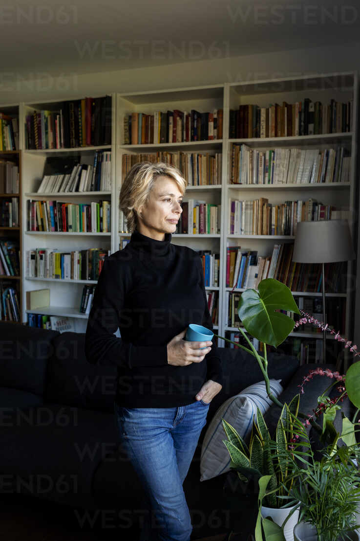 Thoughtful mature woman with cup of coffee at home - VABF02389 - Valentina Barreto/Westend61