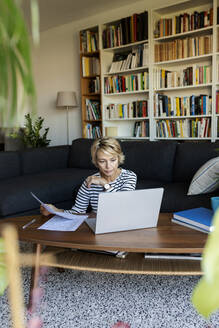 Mature woman with documents using laptop at home - VABF02413