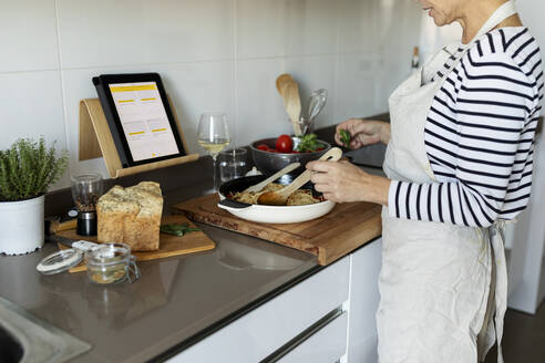 Close-up of woman with tablet cooking pasta dish in kitchen at home - VABF02446