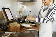 Happy mature woman with tablet cooking pasta dish in kitchen at home - VABF02449