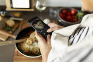 Close-up of woman taking smartphone picture of her pasta dish in kitchen at home - VABF02452