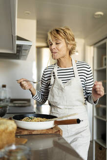 Mature woman tasting homemade pasta dish in kitchen at home - VABF02455