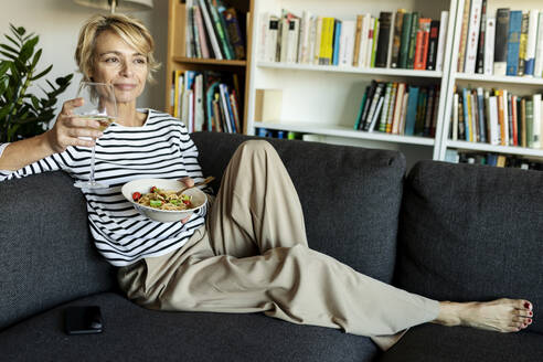 Mature woman eating homemade pasta dish and drinking wine on couch at home - VABF02458