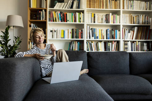 Mature woman using laptop and having lunch on couch at home - VABF02461