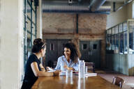 Two young businesswomen talking at conference table in loft office - SODF00353