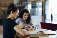 Two young businesswomen working together at conference table in loft office - SODF00356