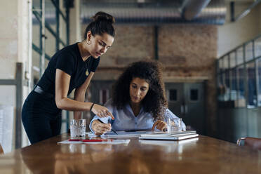 Two young businesswomen talking at conference table in loft office - SODF00359