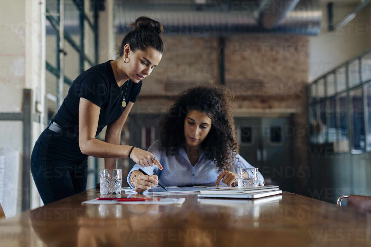 Two young businesswomen talking at conference table in loft office - SODF00359 - Sofie Delauw/Westend61