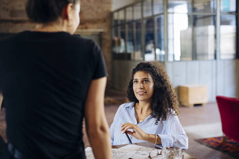 Two young businesswomen at table in loft office - SODF00365