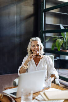 Portrait of smiling mature businesswoman with laptop in loft office - SODF00371