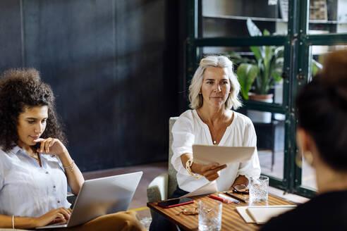 Businesswomen working together in loft office handing over papers - SODF00377