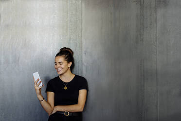 Portrait of happy casual young businesswoman using smartphone in front of a grey wall - SODF00383