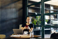 Happy casual young businesswoman with laptop and smartphone in loft office - SODF00392