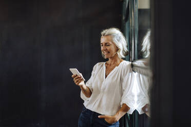 Smiling casual mature businesswoman using smartphone at the window in loft office - SODF00395