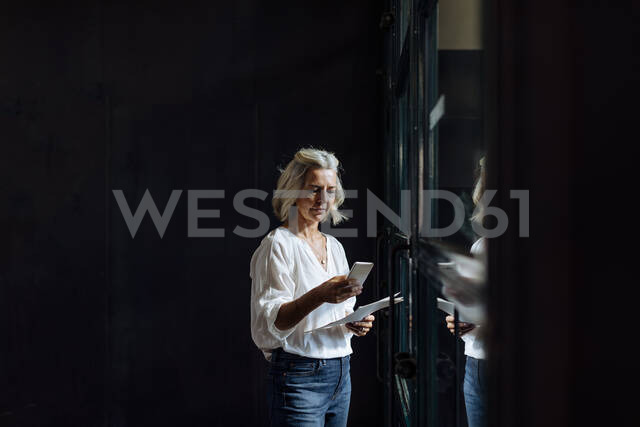 Casual mature businesswoman using smartphone at the window in loft office - SODF00398 - Sofie Delauw/Westend61