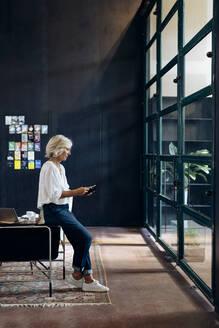 Casual mature businesswoman using smartphone in loft office - SODF00401