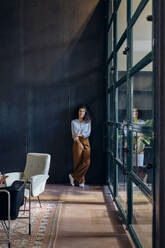 Portrait of young businesswoman standing at the window in loft office - SODF00407