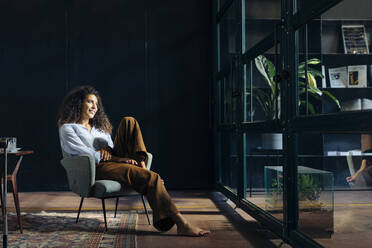 Young businesswoman looking out of window in loft office - SODF00410