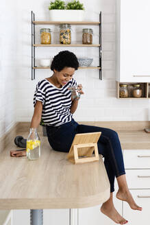 Young woman using tablet and drinking water in kitchen at home - GIOF07782