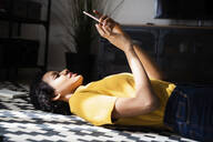 Young woman lying on the floor at home using smartphone - GIOF07785