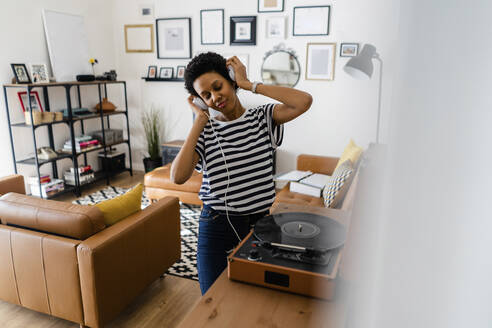 Happy young woman listening to music with headphones and record player at home - GIOF07800