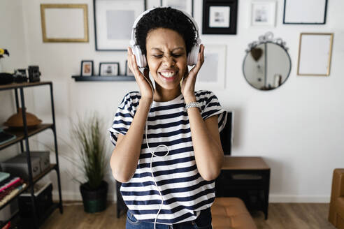 Happy young woman listening to music with headphones at home - GIOF07803