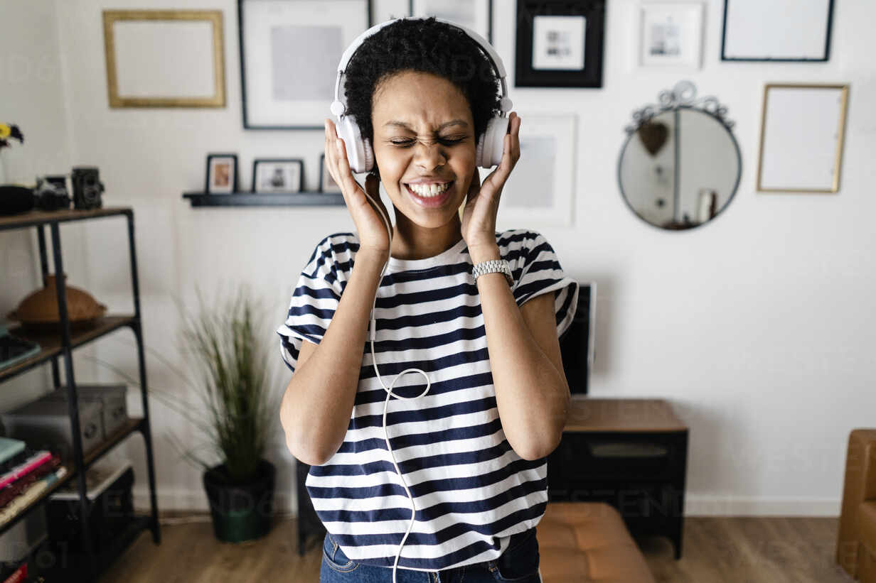 Happy young woman listening to music with headphones at home - GIOF07803 - Giorgio Fochesato/Westend61