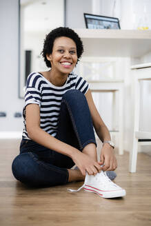 Portrait of happy young woman sitting on the floor at home lacing her sneakers - GIOF07812
