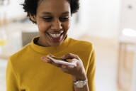Happy young woman using smartphone at home - GIOF07818