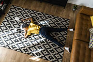 Young woman lying on the floor at home with closed eyes - GIOF07821