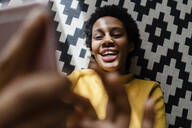 Happy young woman lying on carpet using smartphone - GIOF07827