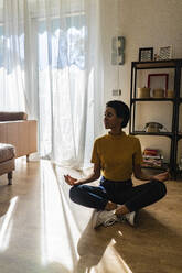 Young woman sitting on the floor at home in yoga pose - GIOF07830