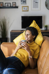 Relaxed young woman lying on couch at home holding mug - GIOF07833