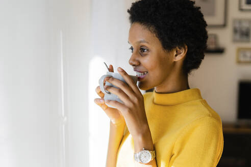Smiling young woman drinking from mug at home - GIOF07836
