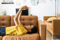 Young woman lying on couch at home using smartphone - GIOF07839