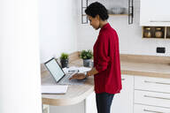 Young woman using laptop in kitchen at home - GIOF07845