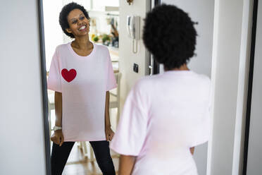 Happy young woman wearing t-shirt with heart shape looking in mirror - GIOF07857