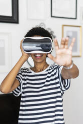 Young woman with VR glasses at home - GIOF07860