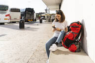 Young female backpacker with red backpack using smartphone, Verona, Italy - GIOF07862