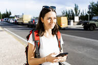 Young female backpacker with red backpack using smartphone in the city, Verona, Italy - GIOF07868