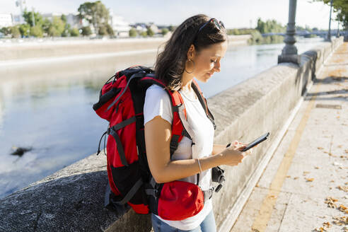 Young female backpacker using smartphone at a river in Verona, Italy - GIOF07871