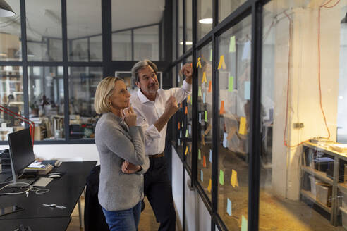 Colleagues looking at sticky notes at glass pane in office - GUSF02687