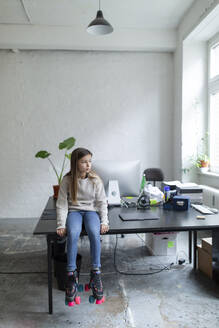 Girl with roller skates sitting on desk in office - GUSF02693