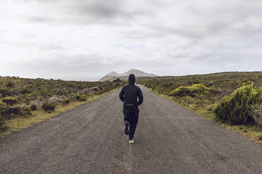 Back view of man jogging on country road, Cape Point, Western Cape, South Africa - MCF00329