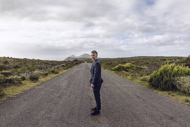 Businessman standing on country road, Cape Point, Western Cape, South Africa - MCF00332