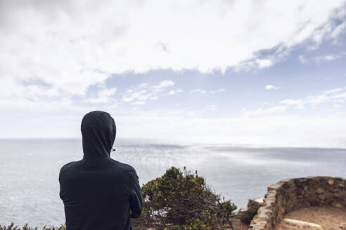 Back view of man wearing hooded jacket looking to the sea, Cape Point, Western Cape, South Africa - MCF00335