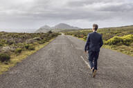Back view of businessman walking on country road, Cape Point, Western Cape, South Africa - MCF00341